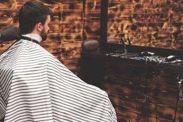 Haircut head in barbershop. Barber cuts hair on the head...