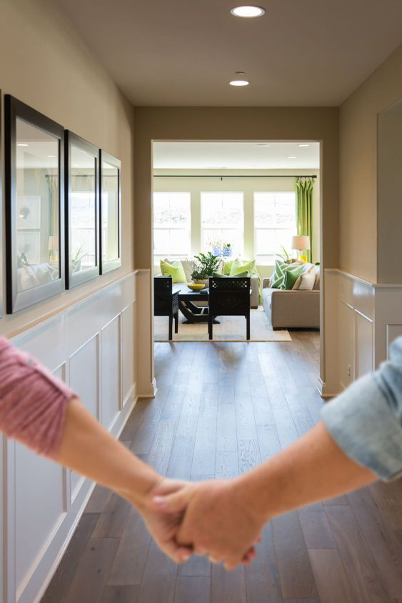 Couple Holding Hands Walking Through Hallway of New House.
