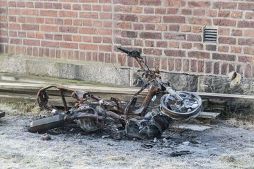 Burnt and abandoned moped on the ground.