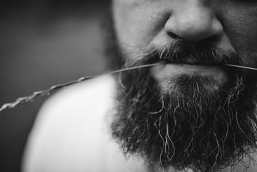 Cropped portrait of a bearded brunette man with a straw...