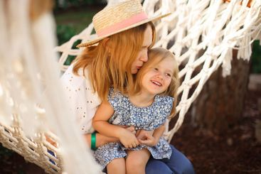 little girl with mom sitting in hammock at sea