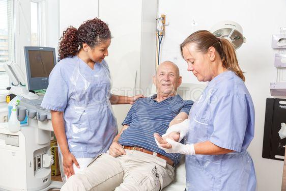 Sköterska sätter plåster på äldre patient