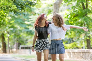 Two girls walking embraced at park.