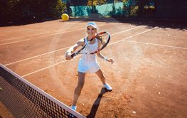Woman hitting the tennis ball on the court