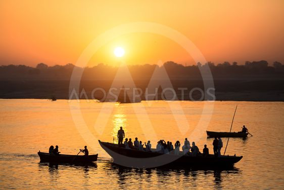 Dawn on the Ganges river, with the silhouettes of boats...