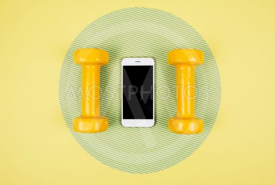 Orange dumbbells with smartphone on yellow and green...