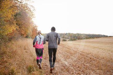 Rear View Of Mature Couple Running Around Autumn Field