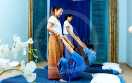 Two thai masseuses synchronously doing thai massage.