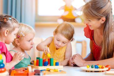 Group of children and teacher playing in kindergarten