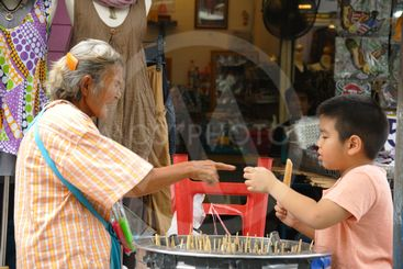 Unknown old woman laughing while selling ice to a boy