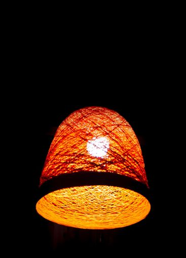 A braided orange retro lampshade with one wooden-style...