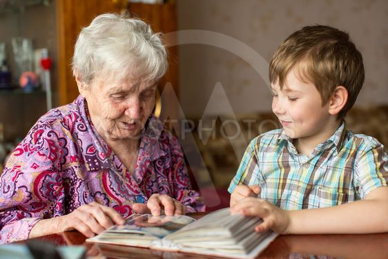 Grandmother and grandson looking photo album.