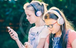 Two teenagers listening to music from smartphones...