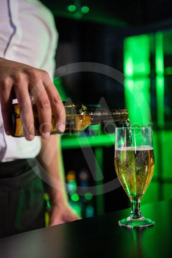 Mid section of bartender pouring beer in a glass
