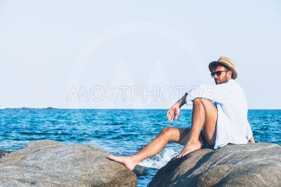 Young man relaxing on the beach, sitting on a rock near...