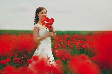 Bride in a white dress with bouquet of red poppies, warm...