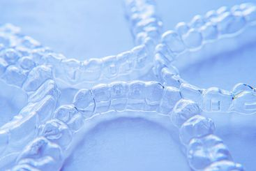 Invisible aligner teeth retainers on a blue background