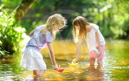 Two little sisters playing with paper boats by a river on...