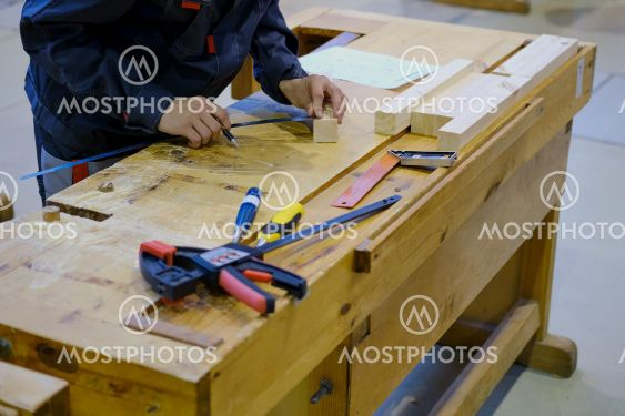 A carpenter measures a bar of wood with a ruler for...