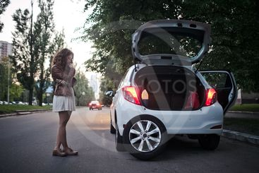 Young girl has problems with the car, wheel replacement