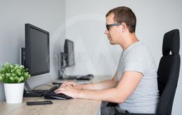 young handsome man using computer in office or home