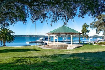 Lush green grassy waterfront park with a quaint little...