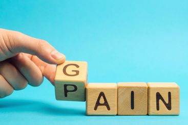 Wooden blocks with the words Gain, pain. Motivation,...