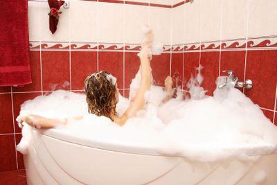Young woman enjoys bath-foam