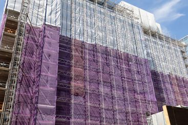 Scaffolding and white and purple sheets.