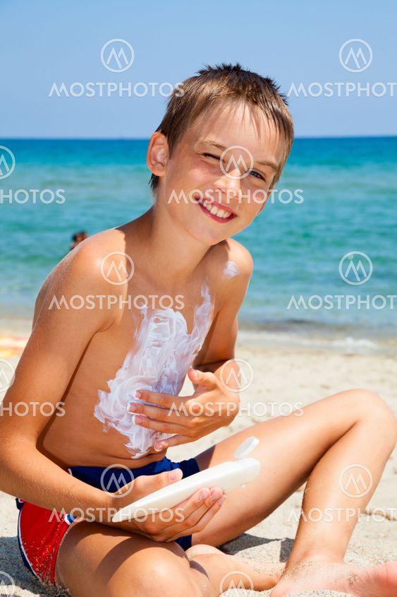 Boy eating melon on a beach