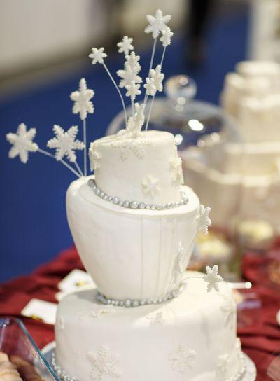 Beautiful wedding cake in white with snowflokes .