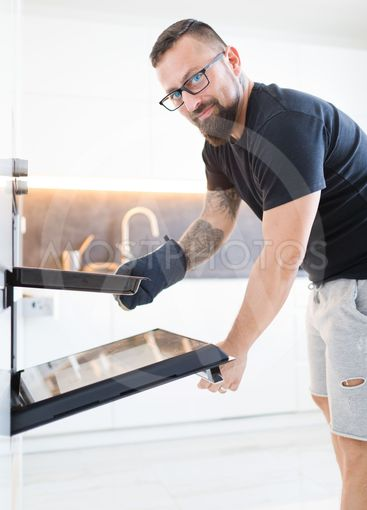 Man with glasses in black T-shirt in modern white kitchen