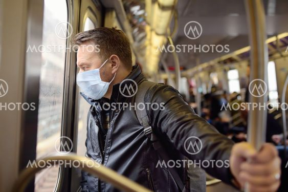 Mature man wearing disposable medical face mask in car...