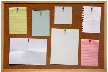 Paper on an isolated cork notice board.