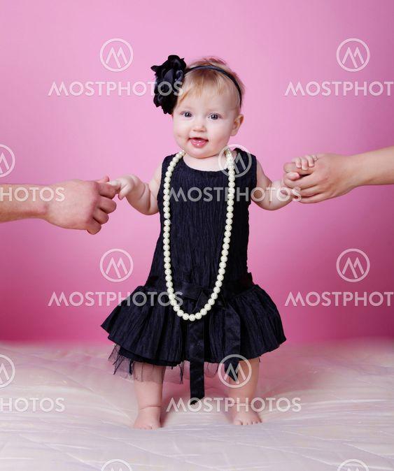 Little girl in black dress in studio