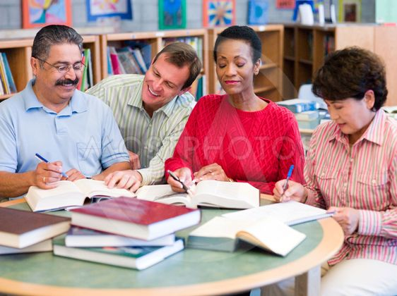Teacher helping mature students in library