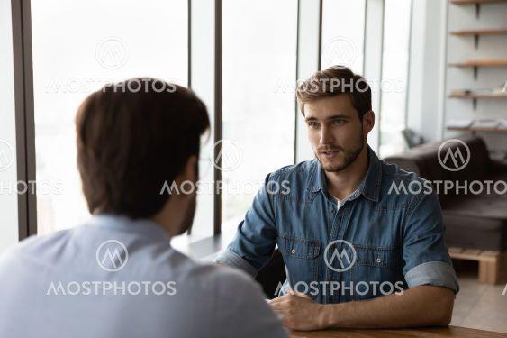 Young Caucasian businessmen talk discuss collaboration...