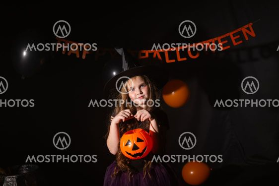 Funny child girl in witch costume for Halloween with...