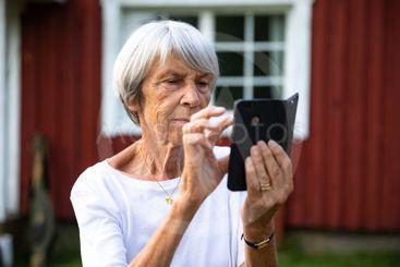 äldre kvinna fotar med telefon