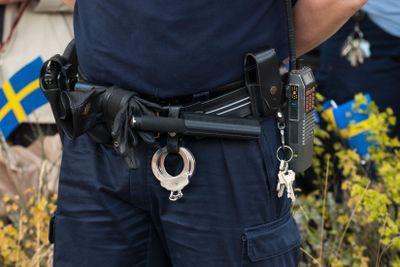 En polis med batong och handklov