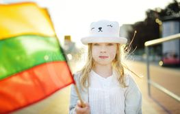 Cute girl holding tricolor Lithuanian flag on Lithuanian...