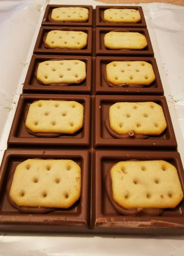 Bar of brown chocolate with salty crackers