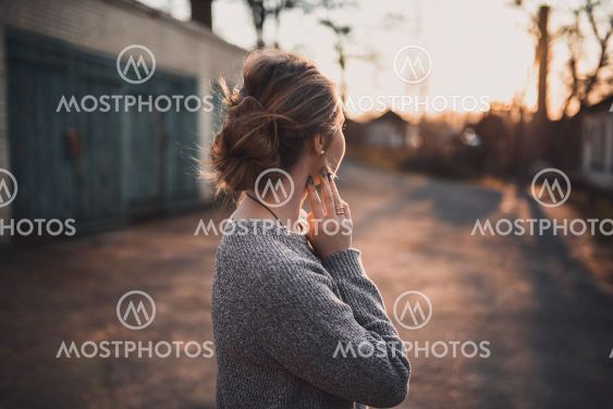 woman with hair tied in a bun in gray knitted sweater On...