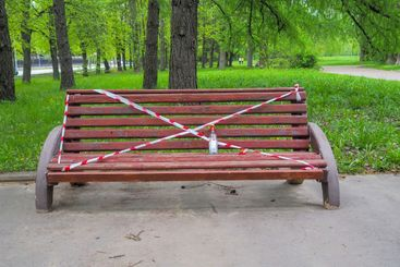 The bench in the city park is wrapped in red and white...