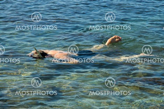 Adult woman diving into clear water of sea