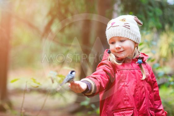 Little girl and great tit bird