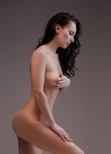 side view of sexy and naked woman isolated on grey