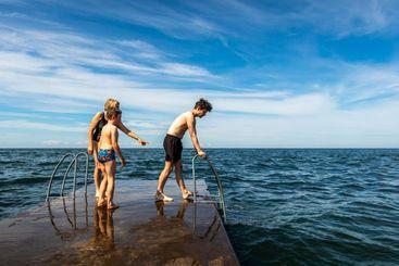 Familj som badar från stenbrygga vid havet.