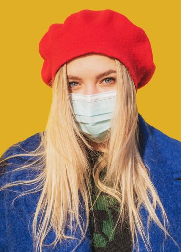 Beautiful girl in a medical mask on a yellow background....