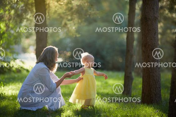 Mother and daughter walk in the Sunny summer forest
